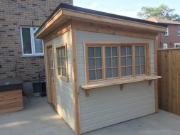 Urban Studio plan 8' x 10' with canexel siding and a flat roof in a backyard seen from front. ID number 5660-1.