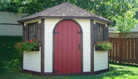 Catalina shed design 8' in a backyard with an arched door seen from the frontage. ID number 1547