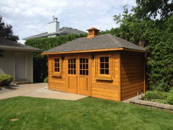 Sonoma pool house design 9 x 16 with double arched deluxe doors in a backyard seen from the frontage. ID number 3107-1.