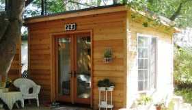 Urban Studio cabin plans 10x12 with french double doors  in a backyard seen from the front. ID number