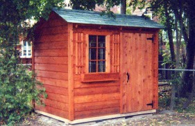 Bar harbor shed design 6 x 8 in a backyard with a standard door seen from the left. ID number 1483-1