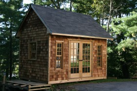 cooper creek garden shed plan 10x14 with cedar shingle siding and double french doors in a backyard. ID number